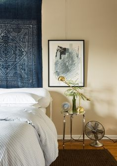 Masculine bedroom with dark blue hues and antique side table