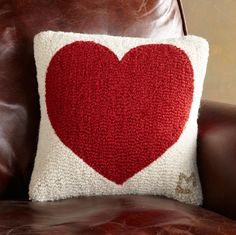 """New Zealand wool is hand hooked—lovingly—in a pillow that radiates heart. Designed and initialed by Vermont artist Laura Megroz. Catalog exclusive. Cotton velveteen back. Polyester fiberfill. Zipper closure. 14"""" sq."""