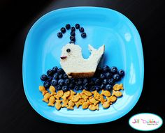 from meet the dubiens      Chicken sandwich cut into whale shape, blueberry eye and craisin mouth. Blueberry water and blueberry coming out of the spout. Goldfish crackers in the 'water.'