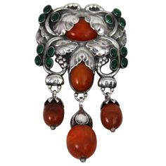"""Georg Jensen Master Brooch no. 96 with amber and green agate. The brooch originially was designed by Georg Jensen in 1912. This brooch measures approximately 4 1/4"""" long and 2 1/4"""" wide. The brooch is in excellent condition and bears impressed company marks for 1910-1925."""