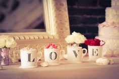 Vintage Valentine Day idea : paint the letters on cheap cups to decorate the table. Fill each one with delicious treats! (Could easily be done for any holiday or event)