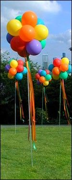 OUTDOOR - LARGE BALLOON POM POM TOPIARY A cluster of twelve air-filled 16-inch balloons tied and twisted together to form a sphere. The balloons are attached to a pole which is driven into the ground or attached to a tent post, fence, or railing.