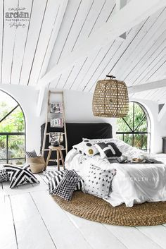 white painted rafters in bedroom opens up the room, love the black and white detail and natural accessories