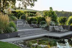 Ein Garten mit viel Wasser: Ein Brunnen mit zwei kubischen Speiern und ein Schwimmteich auf der unteren Ebene des Gartens als Highlight.