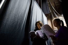 Obama reads over her speech backstage with Kristen Jarvis, director of external relations for the first lady, during a rally at the Strand Theatre in Dorchester, Massachusetts, Oct. 3, 2014.