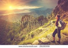 Young traveler with backpack standing on big cliff in the mountains and looks…