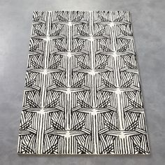 Shop plait rug.   Inspired by the natural pleats and folds that settle on silk fabric, textile designer Fayce created an original pattern in neutral tones of black and natural.