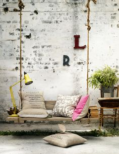 exposed brick painted white with patina. porch spring with throw pillows (natural fabric and bright pink). Foliage, yellow lamp, small chair.