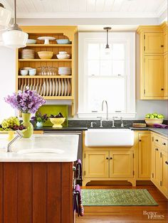 Yellow milk painted cabinets, natural wood floors, farmhouse sink, and industrial style lighting.