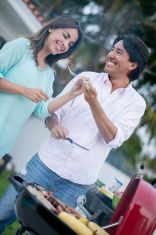 Happy couple hosting a BBQ stock photo