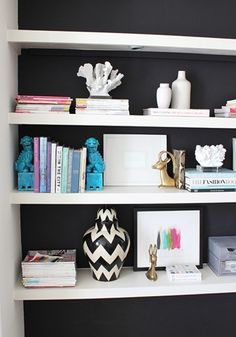 Bright white shelves with dark gray backsplash. Add patterned wallpaper to bookshelf in family room