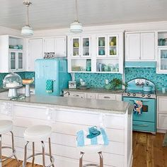 Big Chill appliances in punchy turquoise set the scene for this Caribbean hue-inspired kitchen, where the homeowners selected square glass mosaic tiles in varying sizes and complimentary blues. Select upper cabinets got a rustic touch with wire fronts, wh