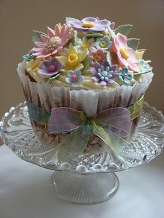 Beautiful cupcake covered in sugar flowers and tied with a ribbon