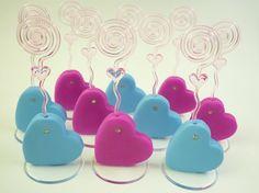 Porta recados corações coloridos, ideais para lembrancinha de festa de noivado. As cores podem ser personalizadas.    Produto sob encomenda. Consulte prazos de produção e envio.  Valor unitário.    Material: biscuit; base acrílica redonda; espiral plástica; detalhe com pedra de strass.  Altura aproximada: 5cm + espiral. R$ 5,00