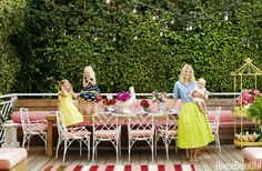 "A banquette runs the width of the backyard deck and can seat a crowd. What color are the cushions? Pink, of course, in a Sunbrella fabric. Custom table surrounded by vintage chairs — ""anytime I see bamboo and Chippendale, I buy it."" The pagoda was rusting when Ewart spotted it at a garage sale and had it powder-coated in chrome yellow. She bought the rug on Etsy.com."