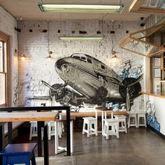 Serving hatches that mimic food trucks pop open from metal façades that front the kitchen space, and crashing in on the Fitzroy venue is a DC-10 from graffiti artist for hire Dan Wenn, trailing street art symbols in its slipstream...