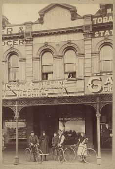 ca. 1885-ca. 1895, View looking across a street to two men, two women, and a boy with bicycles. A woman is looking out the window on the first floor. The signs on the shop read: F.P.C. Beyer Cycle Works. Bicycle Stables. Repairs. Bicycles on hire, repairs. The shop on the left is a confectioners with chocolates in the front window.