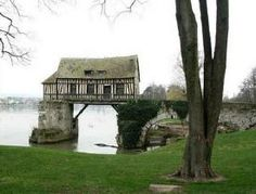 Old mill, that lies stradding two piers of an ancient bridge over the Seine River near Vernon, France