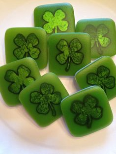 Silver leaf shamrocks (used a hole punch) embedded between reactive Bullseye French Vanilla opaque and a Spring Green translucent 1 1/2 inch squares.  Full fused, cold worked, and sandblasted.  Then put back flat on the kiln shelf on a Slump setting to get the pottery-like matt finish.   Will now add pendant bales.  By Kim Natwig