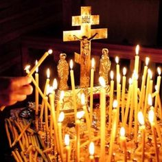 Candles surrounding an Orthodox cross with the Virgin Mary and St John