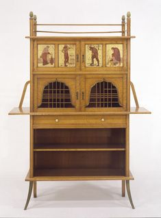 Late 19th c. Aesthetic Cabinet by Edward William Godwin. Materials: Carcase of mahogany, with satinwood (or bird's-eye maple) veneer, brass mounts and epoxy resin handles (replacement of originals); upper doors decorated with four painted and gilt panels.