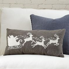 Reindeer in Flight Pillow Cover | White silhouettes of Santa and his reindeer in flight stand out against a graphite background for a festive touch in a neutral palette.