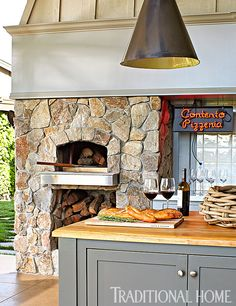 A stone pizza oven in the outdoor kitchen is one of the family's favorite spots. - Photo: John Merkl / Design: Hillary Thomas