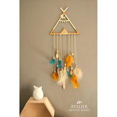 Attrape rêves tipi en bois découpé et gravé dans les tons bleu et moutarde décoré de plumes en bois et naturelles.