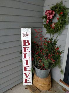 metal planter with a red bow, a sign, and some evergreen foliage in the arrangement #porchIdeas #porch #winter #frontDoorDecor #homeDecor #patiodecor  #Planters