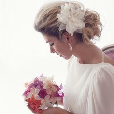 Grampo Kelly para cabelo de noiva com aplique de uma linda flor feita à mão com pétalas de organza, cetim, tule e delicados pistilos de vidrilho. O coque é o penteado para noiva perfeito para esta peça, R$130,00.