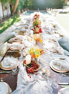 """We incorporated bone china, copper chargers, a mix of copper and bone napkin rings, vintage glassware, hand-dyed silk runners, linen napkins, and a combination of bone and pewter flatware."""" Also added beautiful bowls of fresh summer fruits, gorgeous vibrant colored florals, and an abundance of candlelight to set the mood."""