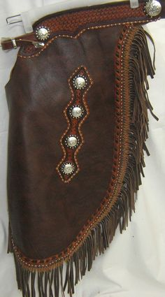 Chaps, the Comancheros mainstay, are worn by major teams in Italy, Europe and the USA . Made from the calf leather, with hand beaten leather accents, buckle closure, reinforced externally with original conchos, meticulously crafted and stitched.