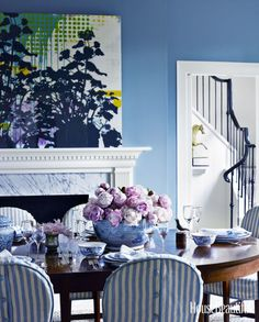 DINING ROOM:  The homeowners entertain frequently in the formal dining room, so chairs are slipcovered. Walls are painted a cheerful hue, Sherwin- Williams's Cosmos.