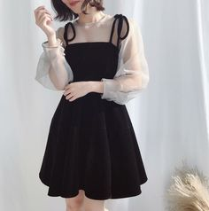 A pretty black dress with white illusion sleeves.