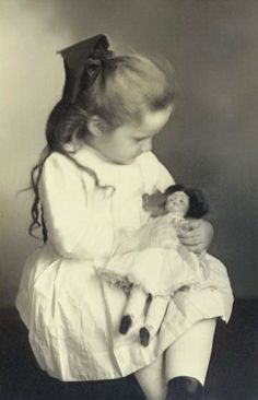 Antique photo of young girl with doll in her lap, circa 1910..