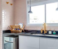 Detalhe da cozinha com torneira tingida de dourado, azulejos rosa que imitam os modelos usados em metrôs europeus e louças lindas trazidas do exterior
