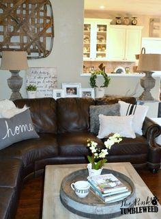 "Love the pillow that says ""home"" and table behind sofa with lamps and pictures."