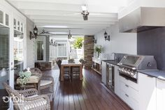 Hamptons style Alfresco/ Outdoor living area. Features a BBQ, lounge area, ceiling fans & heaters, sky lights and bi-fold doors that open into the interior of the home. Custom designed home by Orbit Homes Australia.