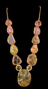 A magnificent necklace featuring eleven Chinese carved tourmalines ranging in color from pink, to green, yellow, and blue, all mounted in 18 karat gold on an 18 karat gold chain. Each toggle carved on both sides with auspicious symbols, including peaches (longevity), bats (happiness), lingzhi (immortality), lotus flowers (purity), double gourds (blessings), various fruit, vegetables, and flowers, and even one with a monkey and peach design.