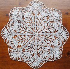 This is a handmade crochet doily. It is made with natural colored thread in size 10. It measures about 18 and has been lightly starched.  Made of cotton.  You can see more doilies here- www.etsy.com/shop/Draiguna?section_id=15792664&ref=shopsection_leftnav_2