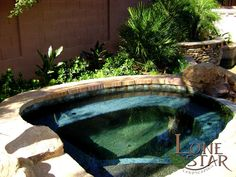 Lush and tropical landscaping around spa with inset boulder in Phoenix, AZ. - www.lonestaraz.com