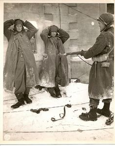 1945--Sergent Clarence Magariea of Carlisle KY, US Infantryman of the 83rd Division holds two captured German SS troopers at bay against a wall in Sart, Belgium. The crossed legs and defiant look of the one on the right and the exposed film thrown down in the snow in front of them make this an interesting picture. Sart was a town where some American army units fell back to after the last great German offensive of the war...In Sart today there is as modest monument to the 82nd Airborne.