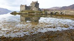 Captured in the west Central Highlands, Scotland. Eilean Donan Castle shimmers in glassy waters. Captured in the west Central Highlands, Eilean Donan Castle shimmers in glassy waters. The attraction dates back to the 13th Century, when the first castle here was built.
