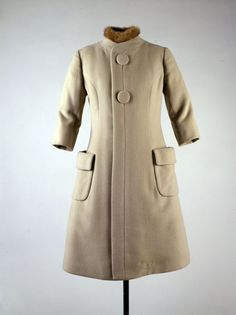 1960. Beige coat. By Oleg Cassini. Made in USA. This coat was worn as part of an ensemble by Jacqueline Kennedy during John F. Kennedy's Inaugural ceremonies in Washington, DC on January 20, 1961