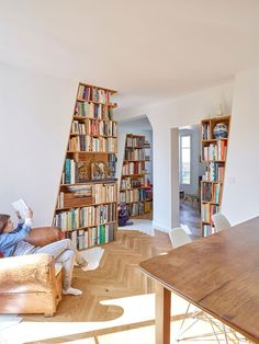 A Parisian flat that includes three connected living spaces that are open but slightly partitioned by built-in bookcases with one angled side.