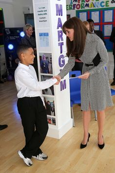 Kate is photographed shaking the hand of a young boy called Kaionel before being given a g...