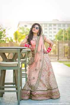 bride wearing aviators, pastel pink lehenga, sequins work, gold broder, copper…