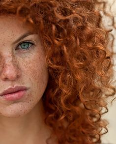 Red head woman ringlet curls and aqua eyes, arched brows, pouty semi chapped low gloss lip, doll face.