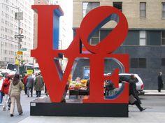"""Dica rápida hoje, principalmente para os casais, é uma """"rápida"""" visita a LOVE SCULPTURE, uma escultura localizada no cruzamento da 6a avenida com a rua 55. Esse símbolo foi criado pelo artista Robert Indiana em 1964 para um cartão de natal. Hoje existem diversas esculturas dessas espalhadas pelo mundo. É um dos símbolos românticos da …"""