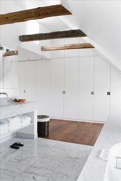Baño con armario integrado. El detalle de las vigas en madera suaviza el estilo.